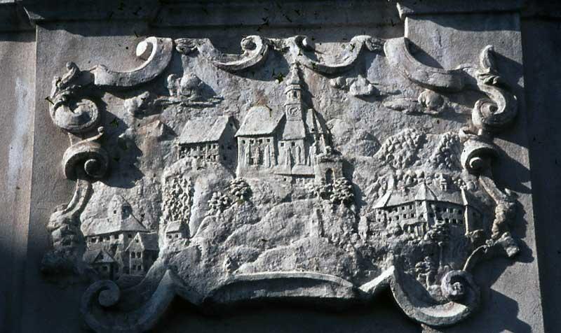 Steinrelief, das in der Stiege zur heutigen Basilika eingelassen ist und die alte Kirche zeigt